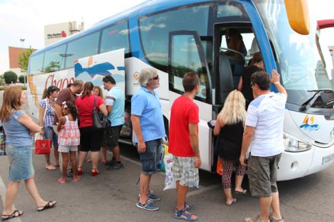 Niños saharauis y miembros de las familias que los han acogido suben al autobús, ayer 16 de agosto, para dirigirse a Barajas  (Foto: Enrique Ayala)
