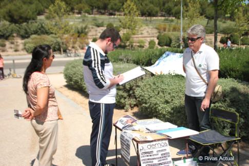 Varias personas firman en la mesa de Podemos esta mañana en el Parque Bellavista (Foto Rivas Actual)