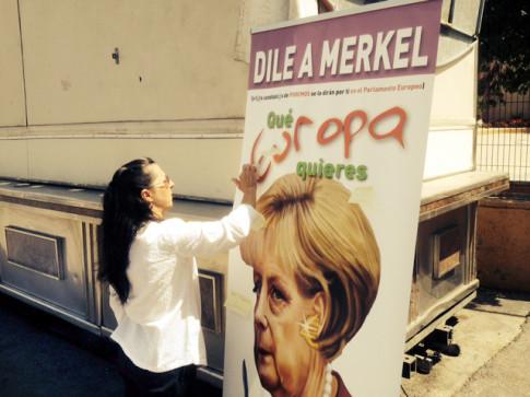 Una persona coloca una pegatina en el cartelón de Merkel (Foto cortesía de Podemos Rivas)