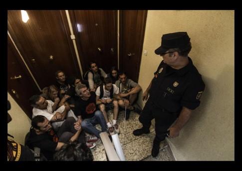 Un policía nacional vigila a varios opositores al desahucio (Foto: DiagonalGlobal.net)