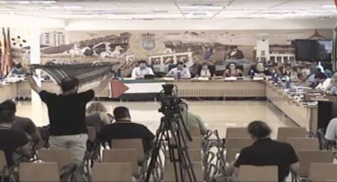 Un momento de la discusión sobre Palestina, con un miembro del público enarbolando una bandera palestina (Foto tomada de la retransmisión en directo del Pleno por Rivasaldía.TV)