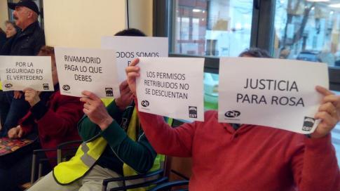 Militantes de ambos sindicatos sostienen carteles alusivos a sus reivindicaciones, durante el último pleno municipal (Foto cortesía de CNT)
